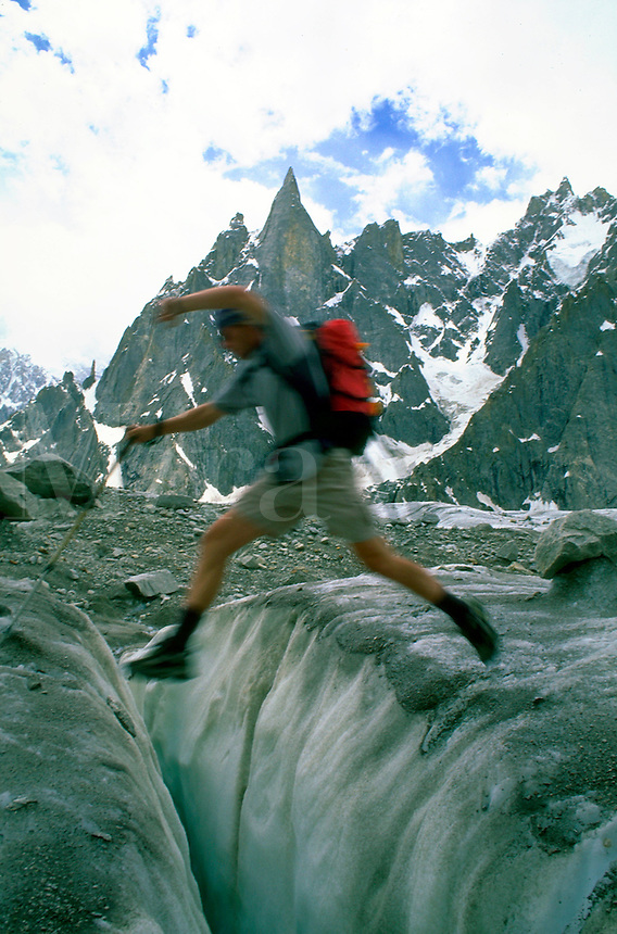 Blurred climber leaping from one rock to another with the Hidden Spires of Karakoram, Pakistan in the background.<br />