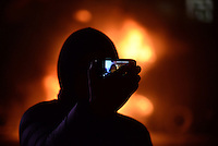 A rioter taki a self portrait with his mobile phone in front of a torched police truck during the   protest against new draconian law to ban the right to  protest across the country.  Kiev. Ukraine
