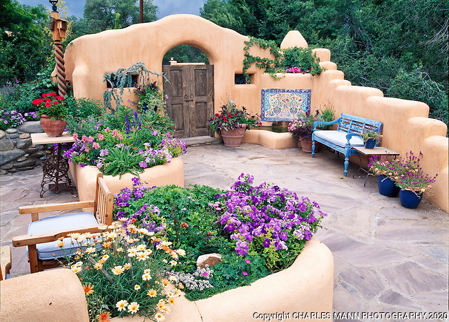 Susan Blevins of Taos, New Mexico, created an elaborate home garden featuring containers, perennial beds, a Japanese themed path and a regional style that reflects the Spanish and pueblo architecture of the area.  The front patio is embellished with a blue bench and colorful container plantings.