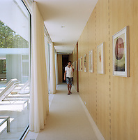 A man talking on the phone walks along the maple-lined corridor which looks out onto the swimming pool