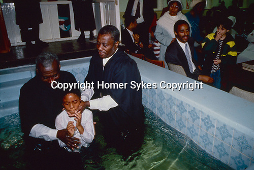 Church of God. In the church hall at Tubbs Road london the pastor and his assistant baptise a young boy. As in most 'born again' churches candidates make their own decision to be baptised by full immersion in the name of the Father , Son and Holy Ghost.