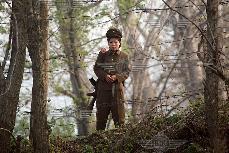 A female soldier stands guard at a post along the banks of the Amrok (Yalu) River, which marks the border between North Korea and China.