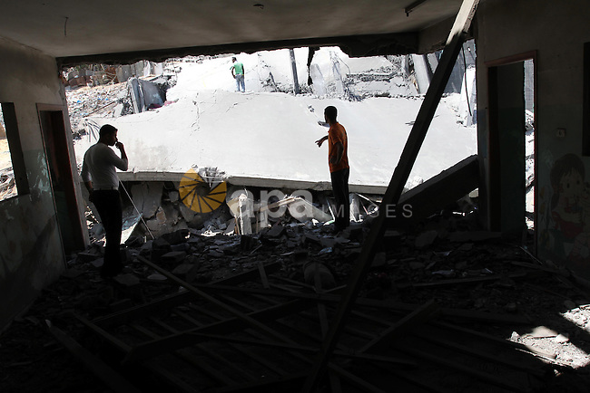 Palestinians inspect the grounds of a sporting club and the homes of some citizens that was destroyed by an overnight Israeli air raid in Beit Lahia, on August 25, 2011. A series of Israeli air strikes on Gaza over the past 24 hours have killed five Palestinians and injured 30, a spokesman for the emergency services told. Photo by Mohammed Asad