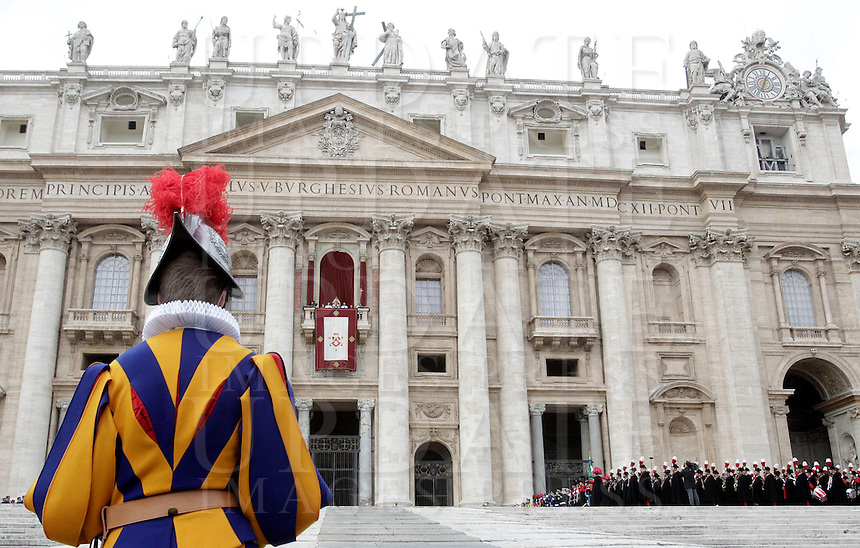 Una Guardia Svizzera durante la benedizione di Natale 'Urbi et Orbi' di Papa Benedetto XVI dalla Loggia centrale della Basilica di San Pietro, Citta' del Vaticano, 25 dicembre 2012..A Swiss Guard stands on as Pope Benedict XVI, background, delivers the Christmas 'Urbi et Orbi' blessing to faithful, from the central Loggia of St. Peter's Basilica at the Vatican, 25 December 2012..UPDATE IMAGES PRESS/Riccardo De Luca