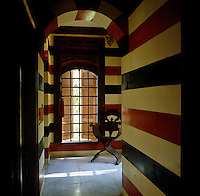 A chair sits by a shuttered window in the corridor of this hammam turned guest house decorated in bold stripes