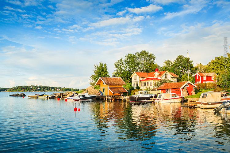 Hus, bryggor och båtar vid Norrhamn Vaxholm i Stockholms skärgård. / Houses, bridges and boats at North Harbour Vaxholm in the Stockholm archipelago.