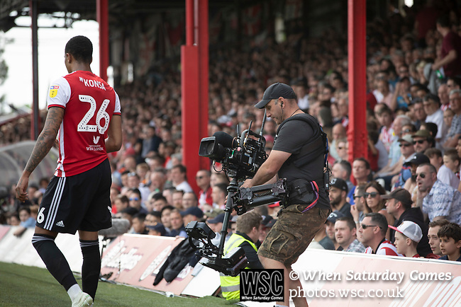 Home defender Ezri Konsa prepares to take a throw watched by a television cameraman in front of the new Road stand as Brentford hosted Leeds United in an EFL Championship match at Griffin Park. Formed in 1889, Brentford have played their home games at Griffin Park since 1904, but are moving to a new purpose-built stadium nearby. The home team won this match by 2-0 watched by a crowd of 11,580.