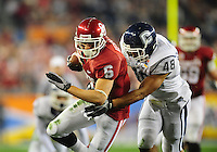 Jan. 1, 2011; Glendale, AZ, USA; Oklahoma Sooners wide receiver (6) Cameron Kenney is pursued by Connecticut Huskies defensive end (48) Trevardo Williams in the first quarter in the 2011 Fiesta Bowl at University of Phoenix Stadium. Mandatory Credit: Mark J. Rebilas-