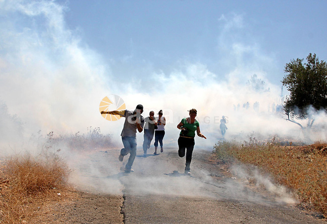 Palestinian and foreign protesters run to cover from tear gas fired by Israeli soldiers during a demonstration against Israel's controversial separation barrier in the West Bank village of Nilin near Ramallah on July 24, 2009. Photo by Issam Rimawi
