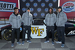 (L-R) Essang Bassey, Malik Grate. Ja'Sir Taylor, and Amari Henderson of the Wake Forest Demon Deacons pose for a photo in front of a NASCAR race car in Victory Circle at the Charlotte Motor Speedway on December 26, 2017 in Concord, North Carolina.  (Brian Westerholt/Sports On Film)