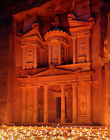 Treasury of the Pharaohs or Khazneh Firaoun, 100 BC - 200 AD, Petra, Ma'an, Jordan. Originally built as a royal tomb, the treasury is so called after a belief that pirates hid their treasure in an urn held here. Carved into the rock face opposite the end of the Siq, the 40m high treasury has a Hellenistic facade with three bare inner rooms. Petra was the capital and royal city of the Nabateans, Arabic desert nomads. Nighttime view with candles lighting up the plaza. Picture by Manuel Cohen