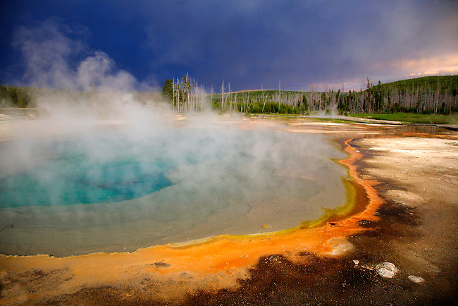 DARK CLOUDS FROM A SUMMER THUNDERSTORM PASS OVER THE BLACK SAND GEYSER BASIN IN YELLOWSTONE NATIONAL PARK,WYOMING