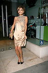 ..May 9th 2012 ..Beverly Hills Caliornia .Bai ling wearing a tan brown  peach Gold dress fake punching a photographer posing smiling throwing hands up in the air.  Feet foot tattoo stars moon star ...AbilityFilms@yahoo.com.805-427-3519.www.AbilityFilms.com.