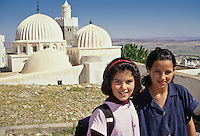 Tunisia, Le Kef.  Two Tunisian Schoolgirls.  Boumakhlouf Mosque (17th Century) in the Background.