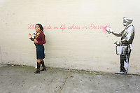 """An NBC reporter does her stand-up in the Woodside neighborhood of Queens in New York on Monday, October 14, 2013 in front of the fourteenth installment of Banksy's graffiti art, """"What we do in life echoes in Eternity"""". The elusive street artist is creating works around the city each day during the month of October accompanied by a satirical recorded message which you can hear by calling the number 1-800-656-4271 followed by  # and the number of artwork.  (© Richard B. Levine)"""