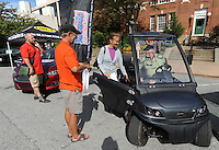 NWA Democrat-Gazette/ANDY SHUPE<br /> Mikel Lolley (from left), co-founder of Sustainable Urban Mobility, helps Fayetteville residents Deborah Bird and Steve Holst Saturday, Sept. 19, 2015, as they try out an electric vehicle during the first electric vehicle rally in downtown Fayetteville. Northwest Arkansas electric vehicle dealers and service providers gathered to give residents a chance to experience and drive the variety of electric vehicles that are available before taking part in a parade through downtown and the entertainment district as a local participation of National Drive Electric Week.