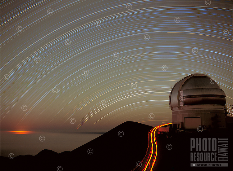 Star trails over the Gemini North Telescope dome, Mauna Kea Observatory, Hawaii.  The glow from lava from the eruption of Kilauea volcano is seen to the left.  The arc in the sky show the paths taken by stars across the sky due to the rotation of the Earth.