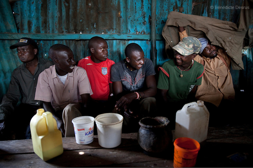 Kenyan men drink Busaa, a traditional fermented beer, at Madiaba Busaa club at midday in a Nairobi slum on April 21, 2013. Busaa is made by crudely fermenting maize, millet, sorghum or molasses. At Kshs 35 per liter it is much cheaper than a Kshs120 half-liter bottle of commercial beer. The local brew was legalised in 2010 and since then Busaa clubs have become increasingly popular in slums and rural areas. Drinking is on the rise in Kenya, especially among young people. Photo by Benedicte Desrus