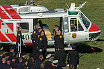 September 20, 2004 Angels Camp, California --Tuolumne Fire –- Fellow crew members of fallen firefighter Eva Marie Schicke stand at attention after loading her casket onto CDF helicopter 404 for her last flight home. The memorial service was held at the Calaveras County Fairgrounds.  The Tuolumne Fire was a small very fast-moving fire that started around noon on September 12, 2004 near Lumsden Bridge at the bottom of the Tuolumne River.  The fire moved rapidly up the 80-plus-degree slope catching Cal Fire Helitack firefighters, tragically killing firefighter Eva Marie Schicke and injuring five others.