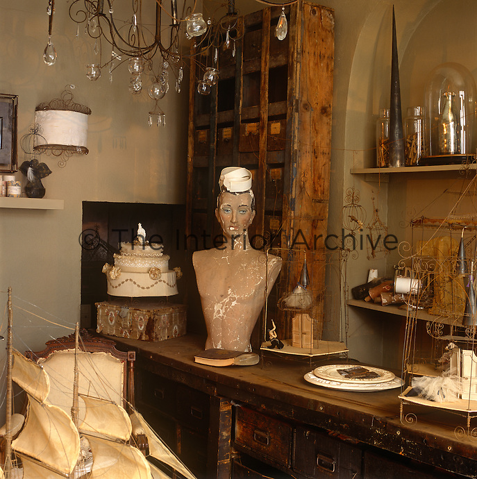 A wire work chandelier with glass candle holders and droplets hangs in a rustic room. A range of eclectic items are displayed on an old battered workbench.
