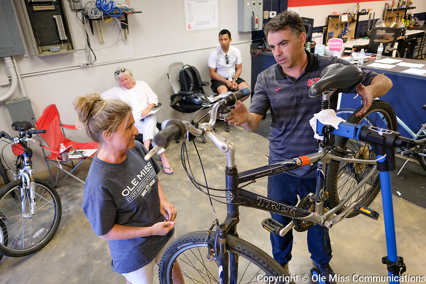 Bicycle technician Stephen Valliant shows Ann Margaret Compton how to replace a brake cable in a bike maintenance class as part of Staff Appreciation Week. Photo by Robert Jordan/Ole Miss Communications