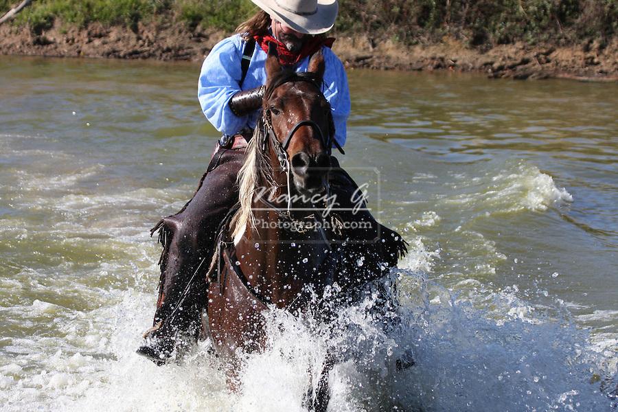 A cowboy running through the water splashing water everywhere