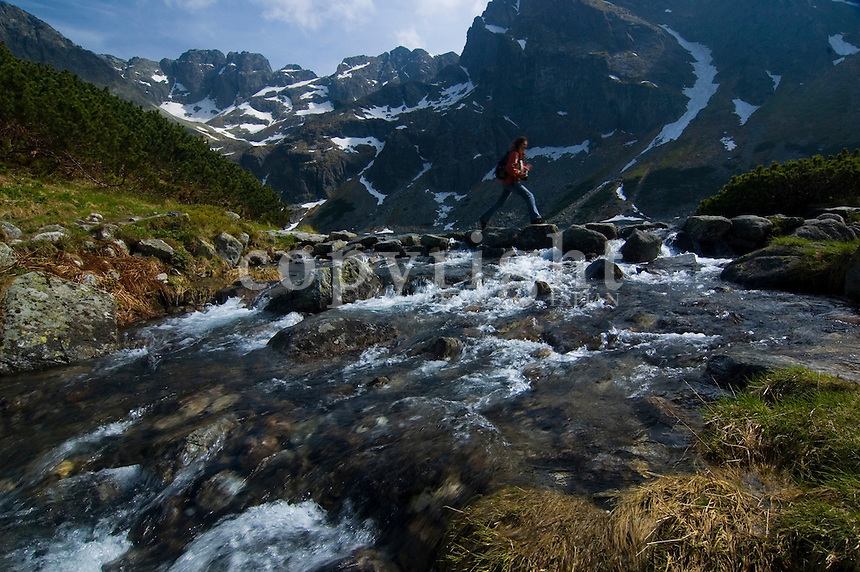 Young girl jumps from stone to stone over the water at the Czarny Staw, Tatra mountains, Poland, Europe