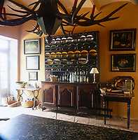 A country yellow kitchen with a stone floor. Green and yellow tableware and bottles of drink are arranged on an antique dresser. An unusual chandelier made from antlers hangs above the kitchen table.