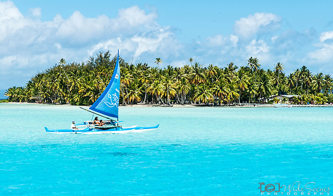 Blue boat sailing in Bora Bora lagoon, French Polynesia