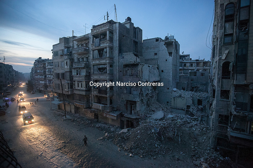 Night falls on a Syrian rebel-controlled area of Aleppo, as destroyed buildings, including Dar Al-Shifa hospital, are seen on Sa'ar street after airstrikes targeted the area a week before. November 29, 2012.
