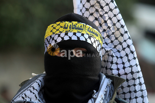 A Palestinian supporter of Fatah movement wears military clothes as they march during a rally on the eve of the 48th anniversary of the formation on the Fatah movement, on December 31, 2012, in the West Bank city of Ramallah. The Fatah anniversary commemorates the first operation against Israel claimed by its armed wing then known as Al-Assifa (The Thunderstorm in Arabic) on January 1, 1965. Photo by Issam Rimawi