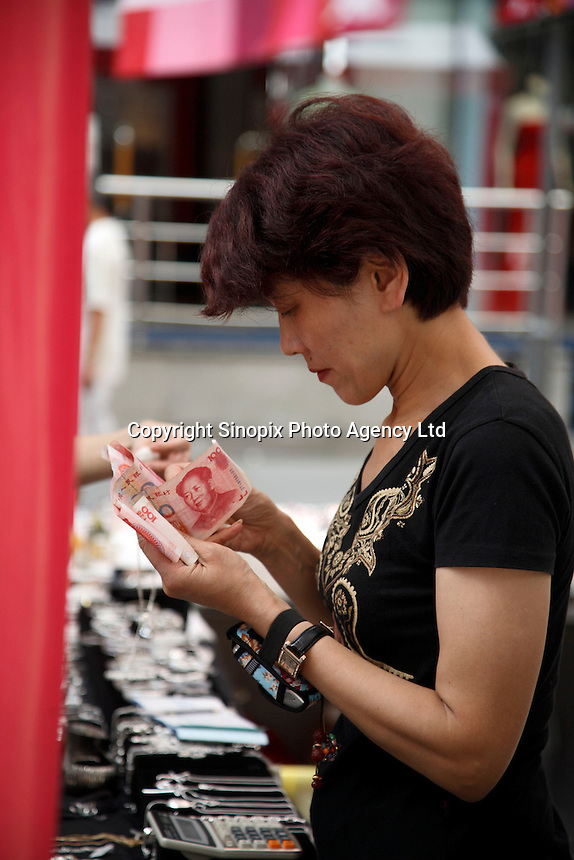 A woman checks for authenticity on a few 100 RMB bills at a market in Shanghai, China..