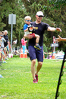 A Chelanman competitor carries his son across the finishline during the multi-sport weekend's Try-A-Tri.