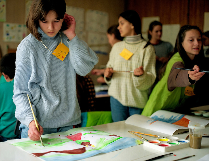 Girls and boys in an art class in a village school in Bosnia. The children are refugees returning to an area which suffered greatly from 'ethnic cleansing'. [Part of a series]