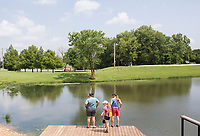 NWA Democrat-Gazette/CHARLIE KAIJO Hannah Cicioni of Rogers, Jude Azzain, 4, Brittany Robison and Alix Means of Tulsa, Okla. (from left) stand on a dock, Friday, July 5, 2019 at the Thaden Fieldhouse across from Lake Bentonville Park in Bentonville. <br /> <br /> Lake Bentonville Park is undergoing a major renovation and will be closed July 8 through spring 2020