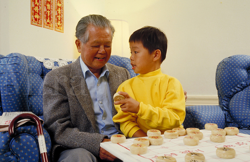 Chinese-American grandfather teaching his grandson the game of Chinese Chess. Oakland, California.