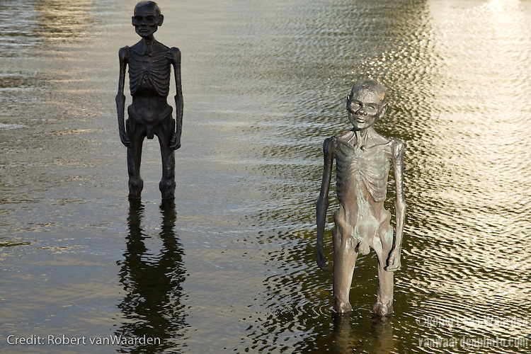 A group of human size sculptures stand in the water at the Bella Center. They represent climate refugees affected by sea level rise. Art work by Sevenmeters.net in Copenhagen for COP 15. An intiative by Danish sculptor Jens Galschiot and his art workshop (Art in Defence of Humanism, AIDOH www.aidoh.dk).