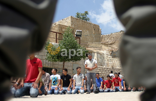 An Israeli soldier stands guard as Palestinians perform the second friday prayer of Islam's holy fasting month of Ramadan outside the Ibrahimi mosque, or the Tomb of the Patriarchs, in the divided West Bank city of Hebron on August 12, 2011.  Photo by Najeh Hashlamoun