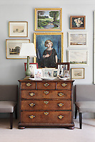 A portrait of a young girl with a string of red beads is an eyecatching  centrepiece above an antique chest of drawers in the sitting room