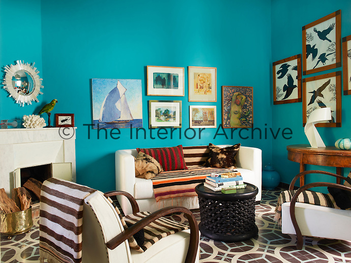 In the vibrant blue living room, the side table is from the 1790s, a Bamileke stool serves as the cocktail table. The fireplace surround is Moroccan marble and the mirror above it is by the Dowe-Sandeses. The sailboat painting is by Mondine and the crow drawings are by Roger Sandes.