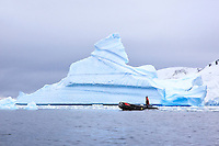 A zodiac provides safety for a group of sea kayakers near Pleneau Island just off the Antarctic Peninsula.