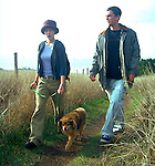 Couple walking dog on trail near Mendocino, California