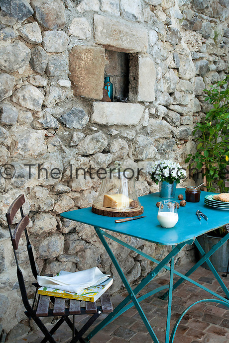 A blue-painted garden table is laid for a simple breakfast on the terrace
