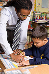 Education Elementary male teacher working with boy in classroom