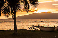 A couple enjoys a Maui beach as the sun sets behind Lanai'i, with an outrigger canoe and a palm tree in the foreground.