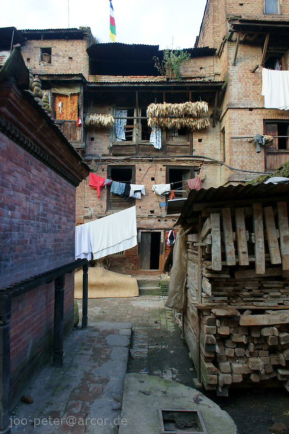 small street in Bhaktapur with backyard atmosphere and typical brick-stone buildings, laundry drying