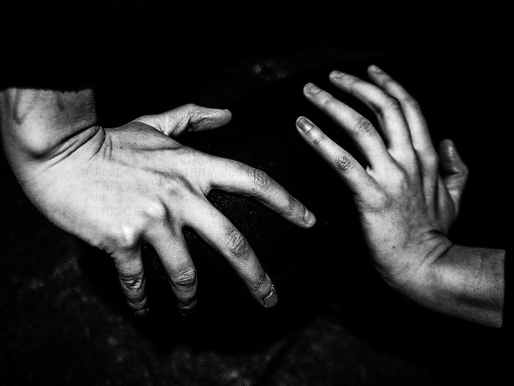 Hands of a young woman against a black background
