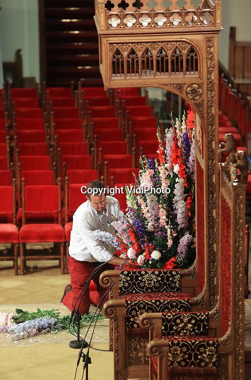 Foto: VidiPhoto<br /> <br /> DEN HAAG &ndash; Met man een macht wordt maandag de Ridderzaal in gereedheid gebracht voor de Verenigde Vergadering der Staten-Generaal. De Haagse bloemenarrangeur Ton Verzijl, legt de laatste hand aan een bloemdecoratie pal naast de troon van de koning. Dit jaar is gekozen voor typische seizoensbloemen als gladiolen, asters, anjers en clematis. De hoofdbloem is de dahlia. In totaal worden voor de decoratie van de Ridderzaal meer dan 3.000 seizoensbloemen in de kleuren rood, roze en lila verwerkt. De goede houdbaarheid van deze bloemen heeft een belangrijke rol gespeeld bij de bloemkeuze. Na Prinsjesdag brengt Verzijl de koninklijke bloemdecoraties naar verzorgings- en verpleeghuizen in de regio Den Haag. Het is het vierde jaar op rij dat de Haagse bloemist de eervolle opdracht krijgt om de Ridderzaal met bloemen te decoreren.