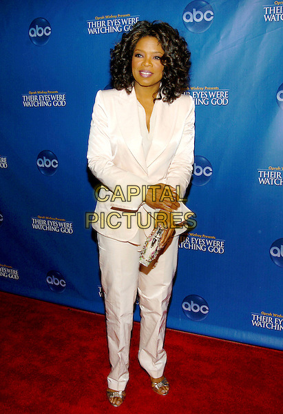 """OPRAH WINFREY.""""Their Eyes Were Watching God"""" Los Angeles Premiere held at the El Capitan Theatre, Hollywood, CA, USA, .3rd March 2005..full length white cream trousers suit jacket  clutch bag.Ref: ADM.www.capitalpictures.com.sales@capitalpictures.com.©Capital Pictures."""