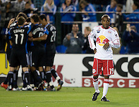 Dane Richards of Red Bull shows disappointment while Earthquakes' players huddle in the background after Gjertsen scored a goal during the second half of the game at Buck Shaw Stadium in Santa Clara, California.  San Jose Earthquakes defeated New York Red Bulls, 4-0.